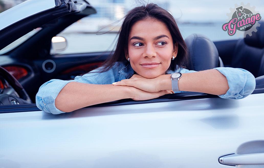 Mujer sonríe por estar limpio su coche